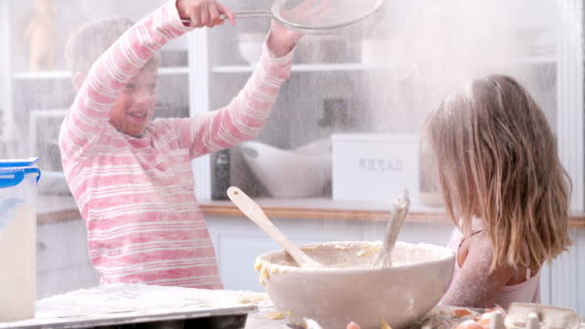 Slow Motion Shot Of Children Having Messy Fun In Kitchen
