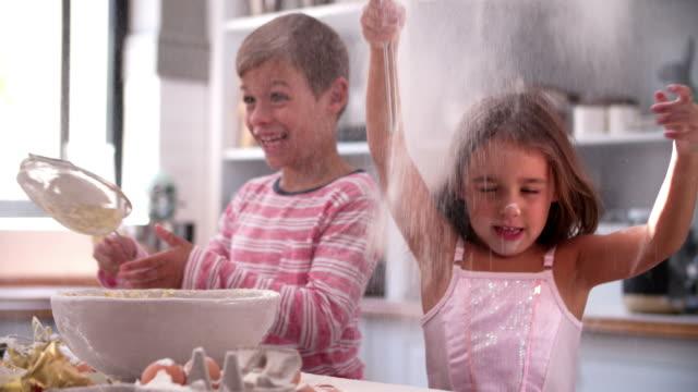 vídeos y material grabado en eventos de stock de slow motion shot of niños que desordenado diversión en la cocina - desordenado