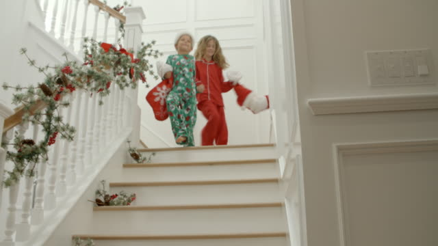 Slow Motion Shot Of Children On Stairs With Christmas Gifts Slow Motion Shot Of Children On Stairs With Christmas Gifts christmas stocking stock videos & royalty-free footage