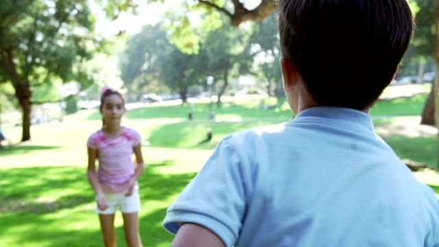 Slow Motion Shot Of niños jugar a atrapar con la bola en el parque - vídeo