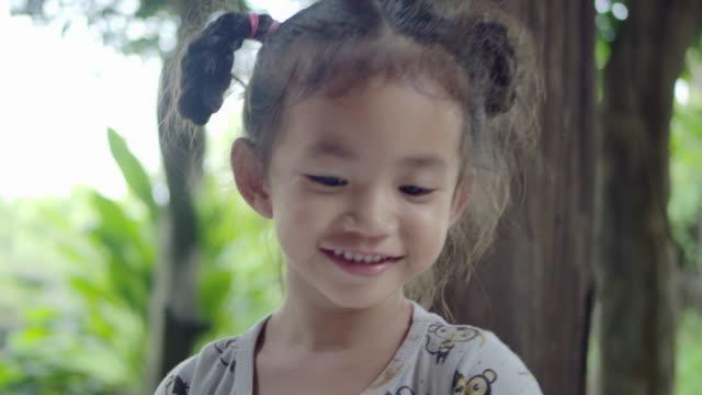 カメラの日に笑顔で屋外で笑う若い女の子をクローズアップのスローモーションショット ビデオ