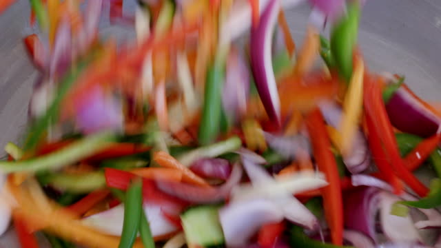 Slow motion shot of colourful thinly vegetables being poured into a pan video