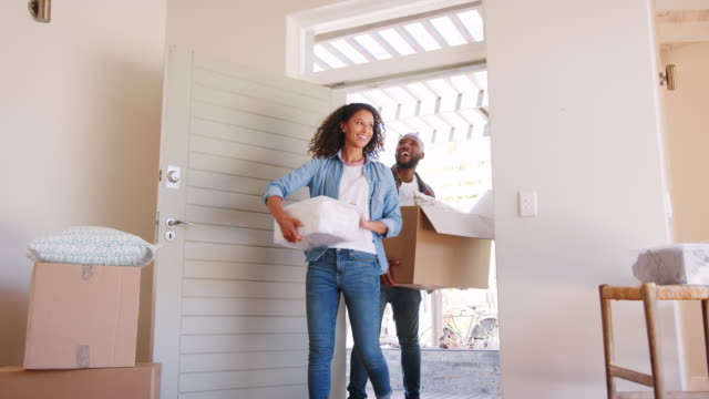 Slow Motion Shot Of Couple Carrying Boxes Into New Home On Moving Day