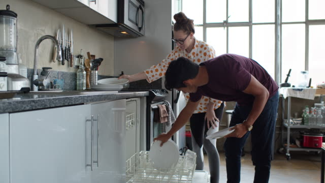 Slow Motion Shot of Couple Loading Dishwasher A young heterosexual couple at home together in their urban loft apartment, loading the dishwasher and cleaning up after a meal. The woman is pregnant. loft apartment stock videos & royalty-free footage