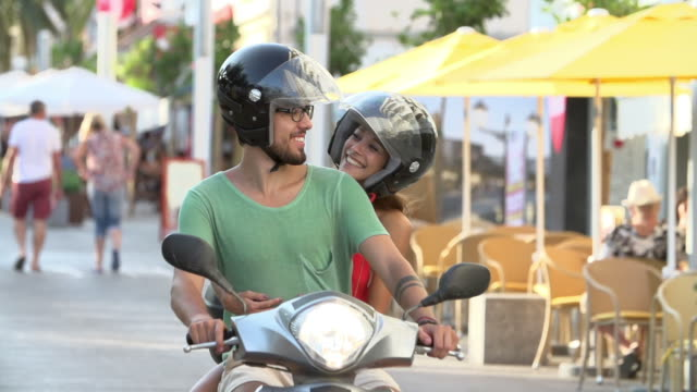 Slow Motion Shot Of Couple Riding Motor Scooter On Road video