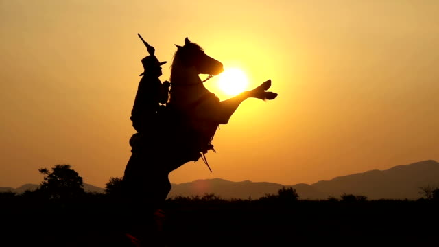 Slow Motion Shot Of Cowboy Horseback Riding And Holding A Gun At Twilight