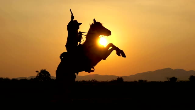 Slow Motion Shot Of Cowboy Riding Horse And Holding A Gun At Sunset
