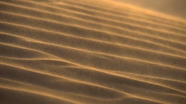 Slow motion shot of Desert sand dunes ripples in the wind