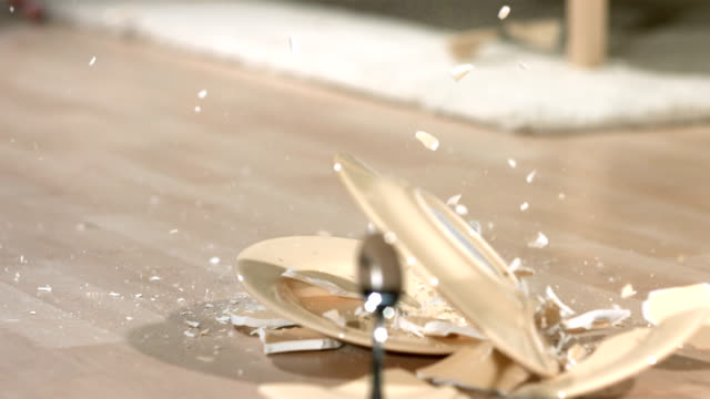 Slow motion shot of dishes falling and breaking, backwards HD 1080p: Slow motion shot of dishes falling and breaking, backwards.  Shot with a high speed camera at 1000 frames per second. breaking stock videos & royalty-free footage