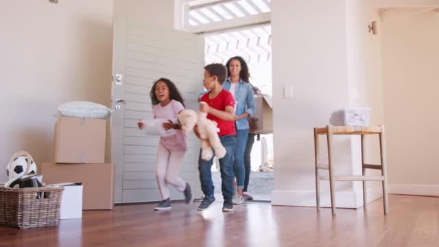 slow motion shot av glada familjen redovisade lådor till nytt hem på flyttdagen - flytta bildbanksvideor och videomaterial från bakom kulisserna