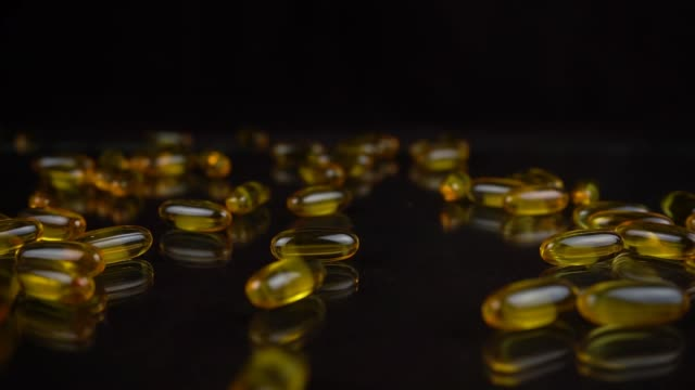 Slow motion shot of falling Omega 3 Fish Oil capsules on black mirror background. Golden color vitamins in gel shell