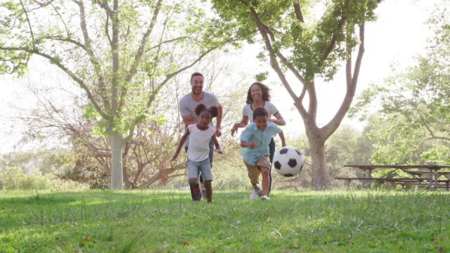 Slow Motion Shot Of Family Playing Soccer In Park Together