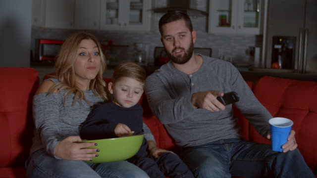 Slow Motion Shot Of Family Sitting On Sofa Watching TV Slow Motion Shot Of Family Sitting On Sofa Watching TV family watching tv stock videos & royalty-free footage
