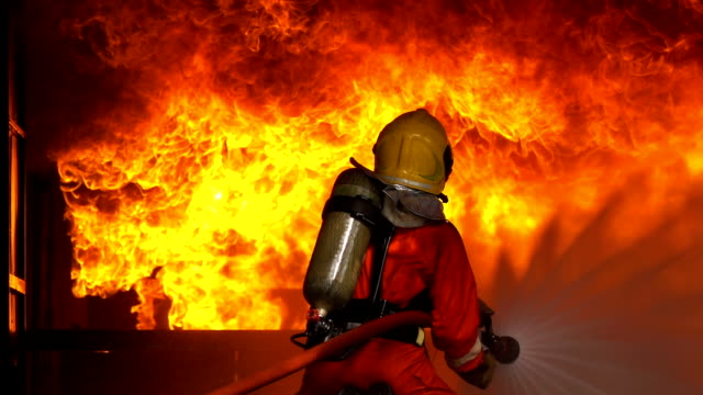 Slow Motion Shot Of Firemen Using Fire Hose To Extinguish A Fire Inside Burning Building