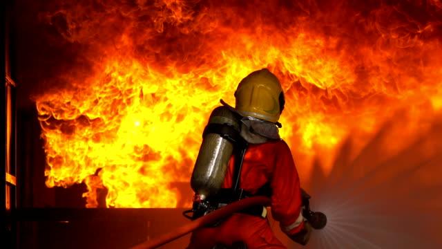 slow motion shot av brandmän som använder brand slang för att släcka en brand inuti brinnande byggnad - släcka bildbanksvideor och videomaterial från bakom kulisserna