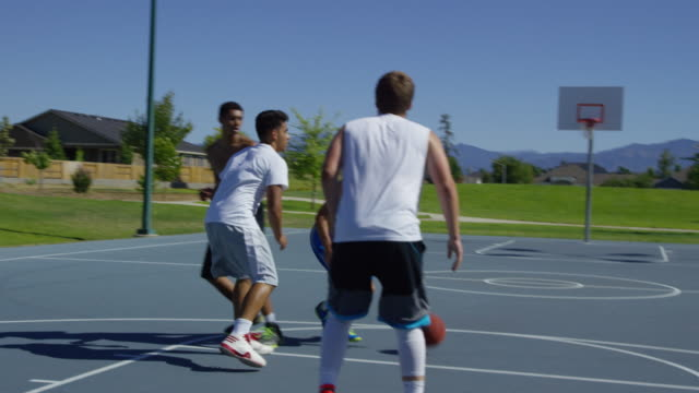 Slow motion shot of friends playing basketball at park video