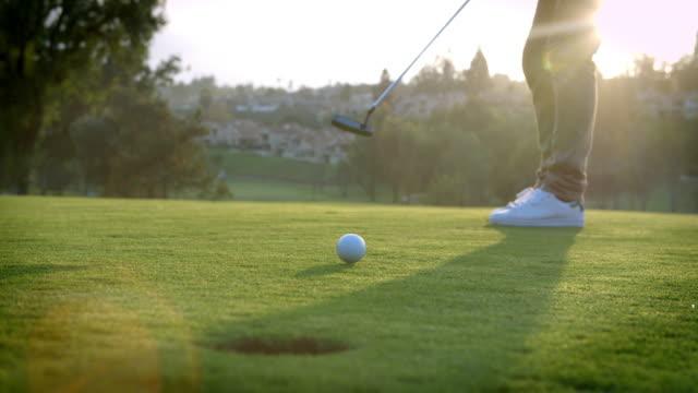 Toma en cámara lenta de golf en el Poner Bola en orificio pasante en verde - vídeo