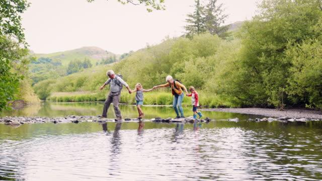 slow motion shot of grandparents helping grandchildren to cross river whilst hiking in uk lake district - nonna e nipote camminare video stock e b–roll