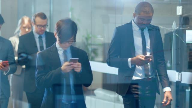 slow motion shot av gruppen av seriösa affärsmän / brottslighet advokater gå genom corporate byggnad hallen. illavarslande, brutala ansikten. blå nyans / skiftning kamera filter. - gemensam samlingsplats bildbanksvideor och videomaterial från bakom kulisserna
