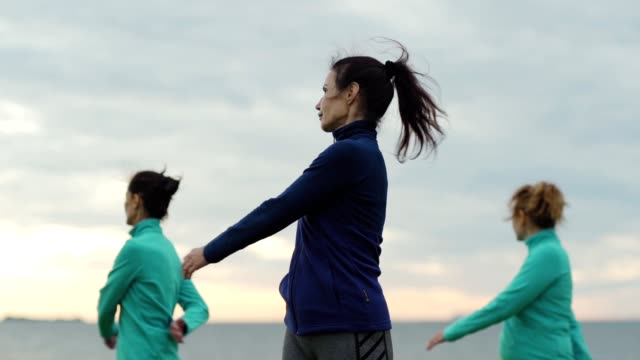 slow motion shot of group of three mature women doing warm-up torso twist exercise before practicing yoga outdoors, yoga teacher standing in the middle - tułów filmów i materiałów b-roll