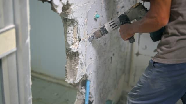 slow motion skott av jackhammer borrning i en vägg och vitt kakel - construction workwear floor bildbanksvideor och videomaterial från bakom kulisserna