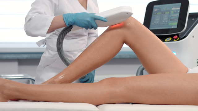 Slow motion shot of Laser hair removal procedure on female legs. video