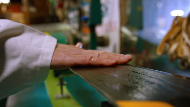 slow motion shot of male ski technician's hand feeling and inspecting the bottom of a downhill ski in an indoor repair shop - negozio sci video stock e b–roll