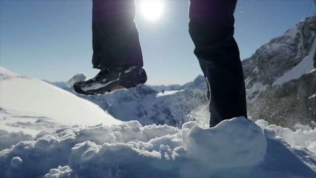 slow motion shot of man walking in snowy alpine environment at sunny day - trekking sul ghiaccio video stock e b–roll