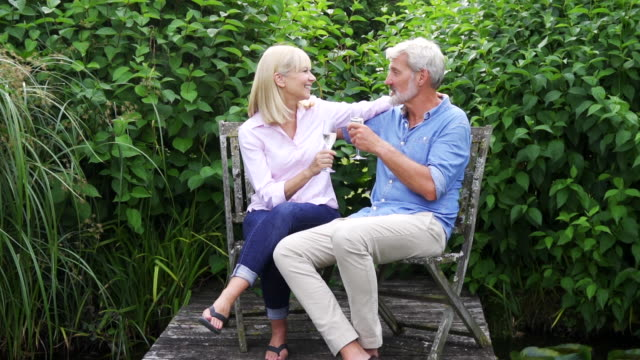 Slow Motion Shot Of Mature Couple Celebrating With Champagne On Wooden Jetty By Lake