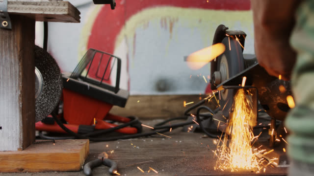 vídeos de stock e filmes b-roll de slow motion shot of metalworker using bench grinder - moedor