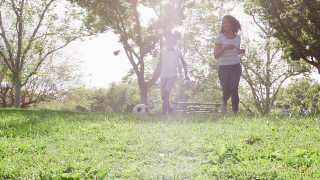 vídeos de stock e filmes b-roll de slow motion shot of mother and daughter playing soccer in park together - pai solteiro