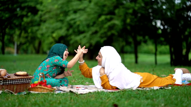 slow motion shot of muslim mother and daughter giving high five together at beautiful park - cultura del medio oriente video stock e b–roll