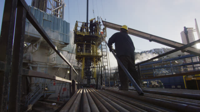Slow Motion Shot of Oilfield Workers Rigging Up Drilling Pipe on a Tall, Metal Platform at an Oil and Gas Drilling Pad Site on a Cold, Sunny, Winter Morning