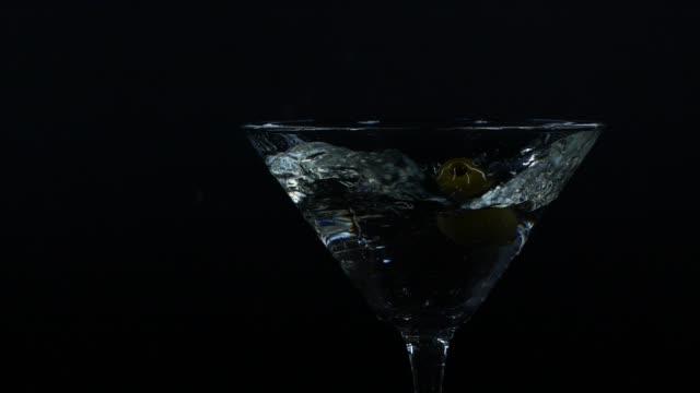 stockvideo's en b-roll-footage met langzame motiedie van olijf die neer in een glas martini valt - martiniglas