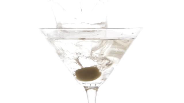 stockvideo's en b-roll-footage met langzame motie die van olijf wordt ontsproten die neer in een glas martini valt - martiniglas