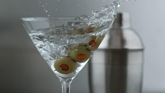 stockvideo's en b-roll-footage met slow-motion shot van olijven in martini spatten - martini