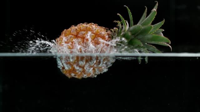 Slow motion shot of pineapples splashing into water