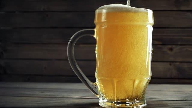 vídeos de stock e filmes b-roll de slow motion shot of pouring beer into beer mug. over wooden background - barrica