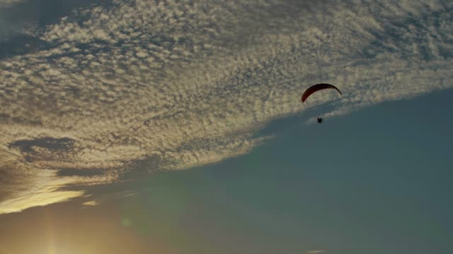 slow motion shot of powered paraglider flying in the sky at sunset - парапланеризм стоковые видео и кадры b-roll