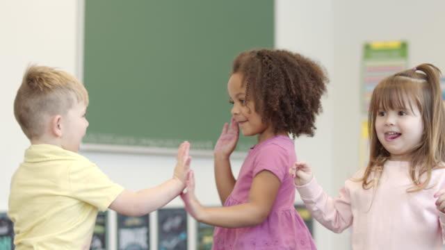 vídeos de stock e filmes b-roll de slow motion shot of preschool children playing and hugging each other - criança pequena