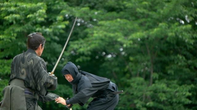 Slow motion shot of Samurai and Ninja on the bridge. Slow motion shot of Samurai and Ninja on the bridge. ninja stock videos & royalty-free footage