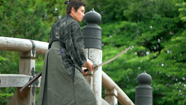 橋の上の侍のスローモーション撮影。 - 戦う点の映像素材/bロール