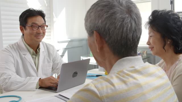 al rallentatore girato di coppia anziana con medico riunioni - cultura coreana video stock e b–roll
