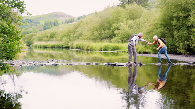 slow motion shot of senior couple using stepping stones to cross river whilst hiking in uk lake district - coppia anziana video stock e b–roll