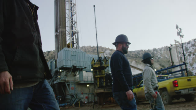 Slow Motion Shot of Several Male Oilfield Workers Walking through an Oil and Gas Drilling Pad Site on a Cold, Winter Morning