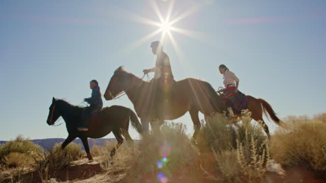 vídeos de stock, filmes e b-roll de tiro em câmera lenta de várias crianças nativas americanas (navajo) montando cavalos através do deserto do vale monumento com seus cães de estimação no arizona/utah em um dia claro e brilhante - cavalgar