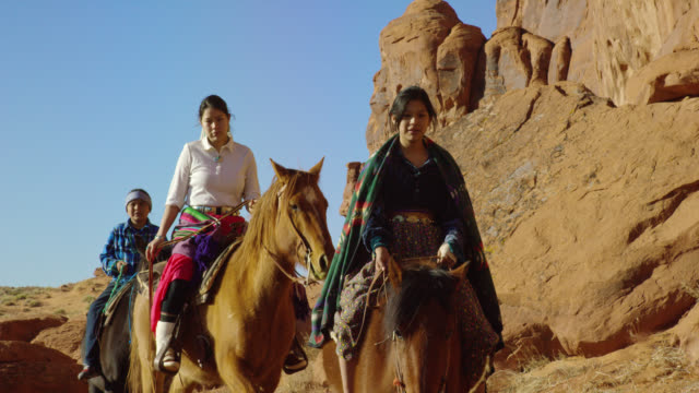 slow motion shot of several young native american (navajo) people riding horses through the monument valley desert in arizona/utah next to a large rock formation on a clear, bright day - attività equestre ricreativa video stock e b–roll