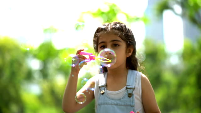 Slow Motion Shot Of Smiling Girl Playing With Soap Bubbles