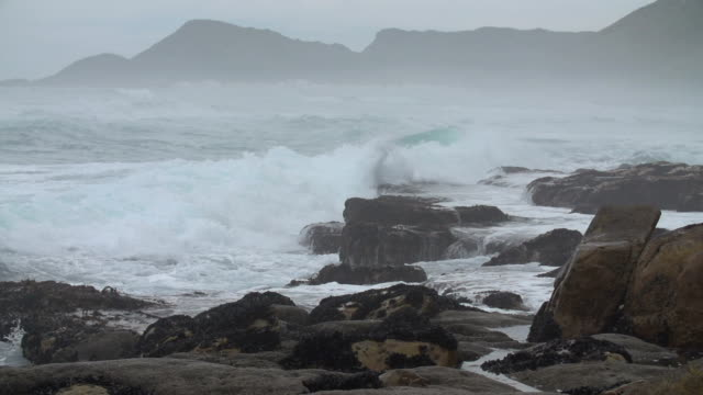 Slow motion shot of stormy waves crashing over a rocky beach in Scarborough, South Africa Slow motion shot of stormy waves crashing over a rocky beach in Scarborough, South Africa. Mountains visible in background, with mussels covering some rocks cape peninsula stock videos & royalty-free footage