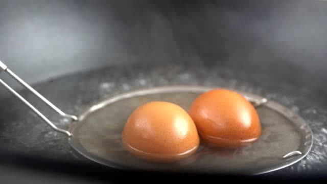 slow motion skott av med kokt ägg av kokt vatten. närbild makro fotografering - kokat ägg bildbanksvideor och videomaterial från bakom kulisserna